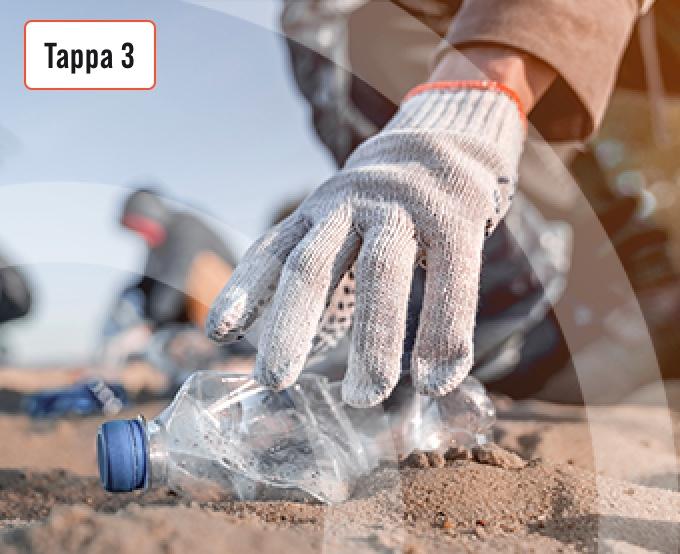 Mani con guanti che raccolgono una bottiglia di plastica in spiaggia