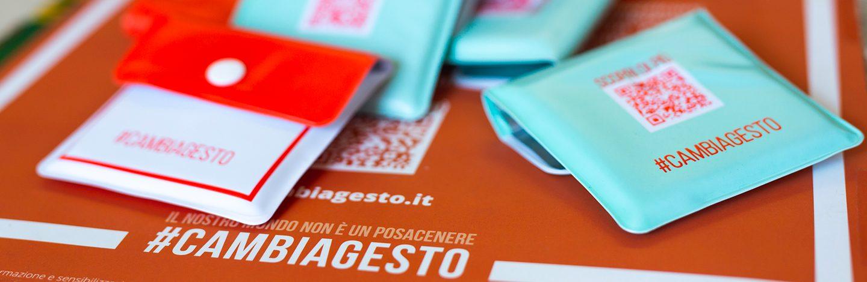 Vari portamozziconi distribuiti sopra al tavolo di una tabaccheria, appoggiati sopra al manifesto della campagna