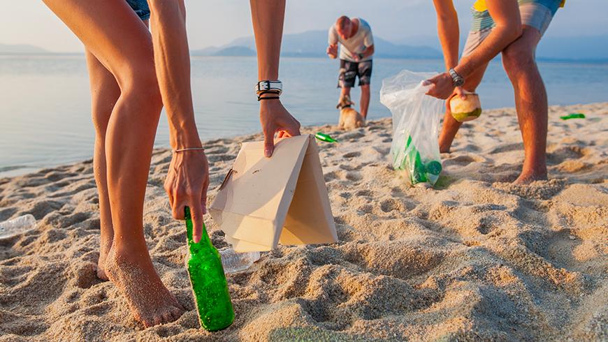 Immagine di persone che raccolgono rifiuti dalla spiaggia