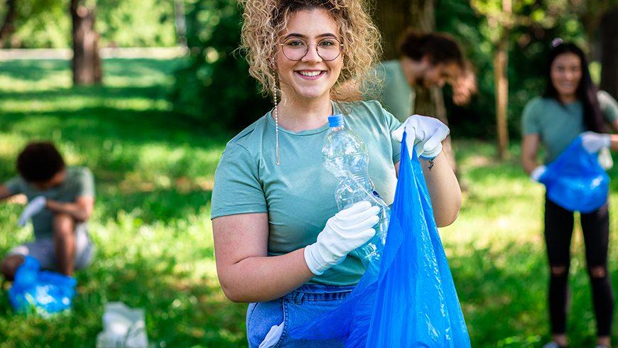 Immagine di una ragazza che raccoglie rifiuti